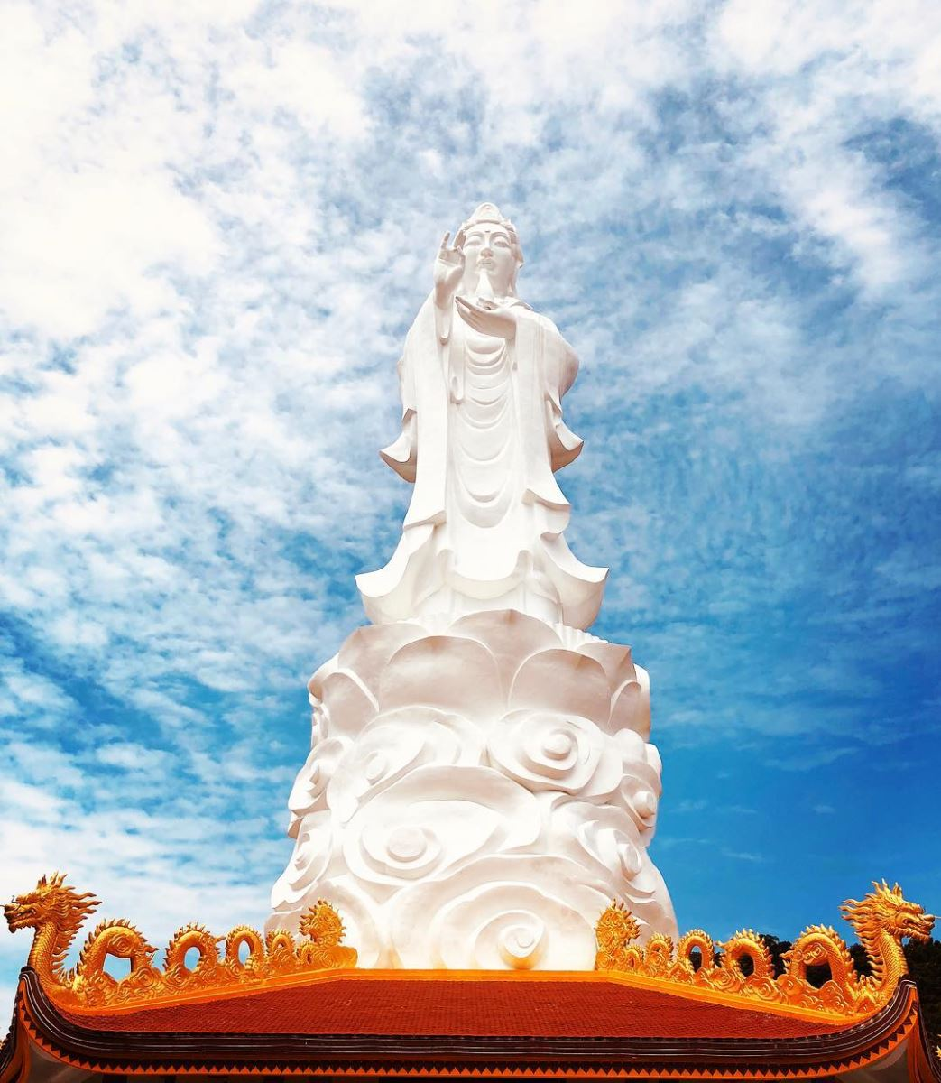 Tall Bodhisattva statue in the middle of the clear blue sky